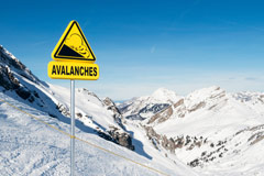 Avalanche sign on top of mountain warning snowmobilers