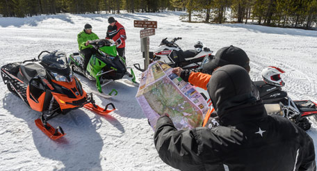 Snowmobilers looking at a map on a trail