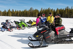 Snowmobilers on trail looking at map