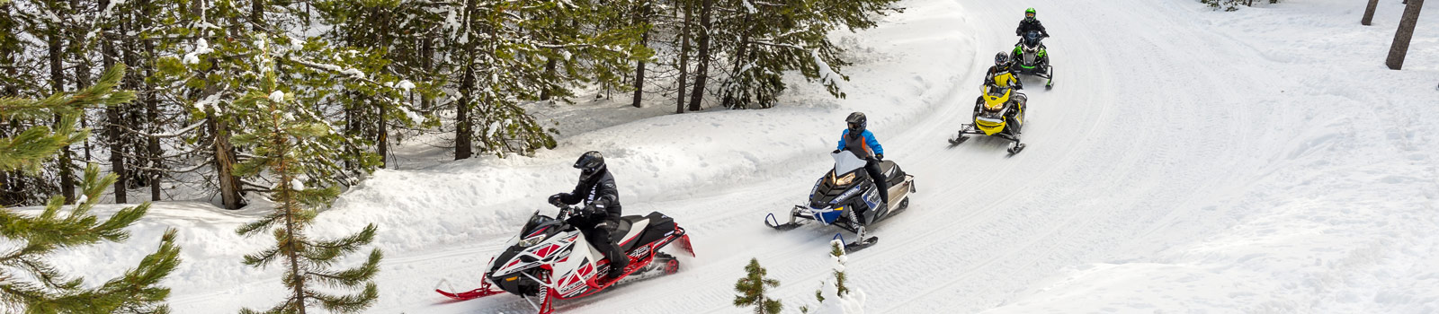 Snowmobilers riding trails