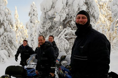 Group of snowmobilers in snow-laden trails