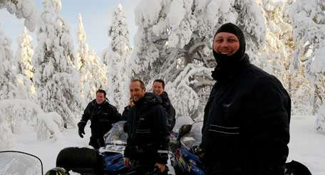 Group of snowmobilers standing next to snowmobiles