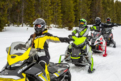 Snowmobilers riding trails showing hand signals